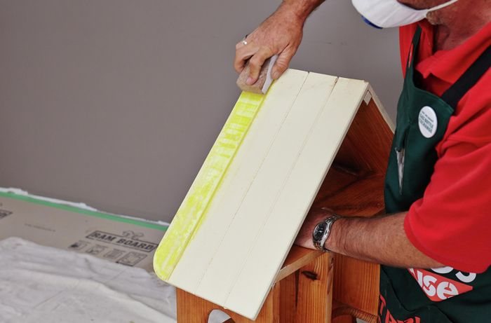 Sandpaper being used to remove paint from a painted bevelled roof of a display frame
