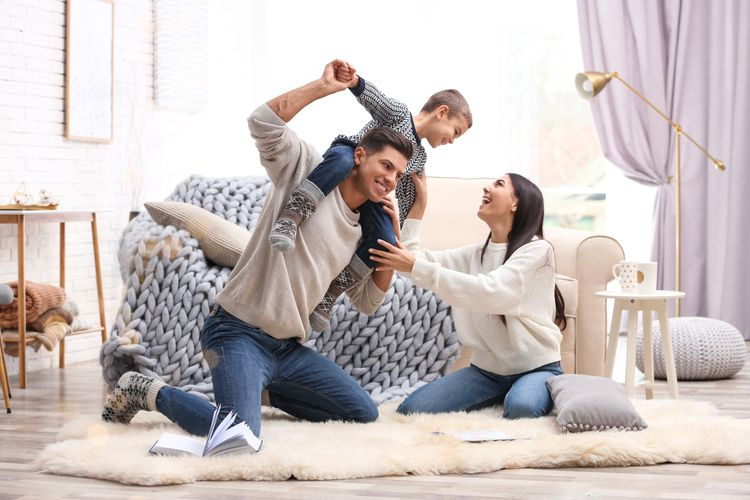 family playing with child on rug in lounge room