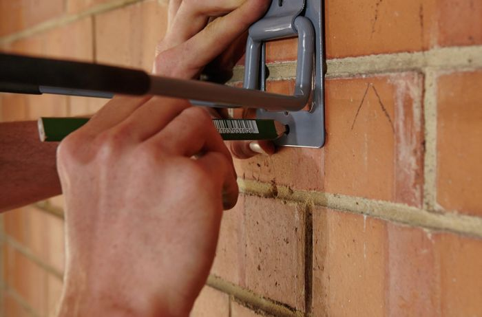 A person marking a hole for a bicycle hook on a garage wall