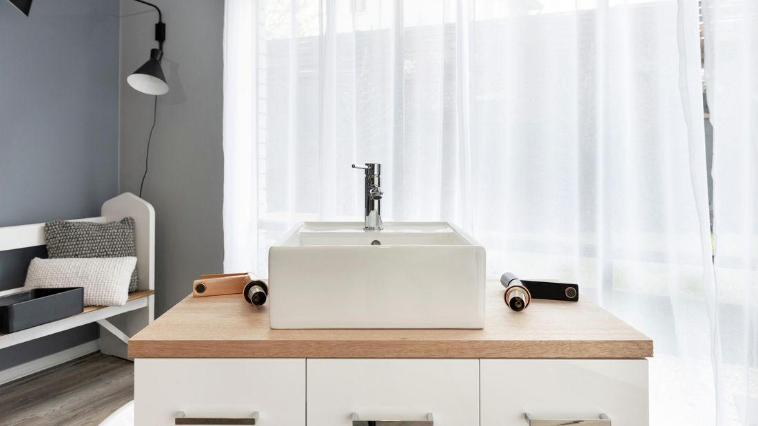 A white, square basin sitting on top of a timber-topped vanity unit
