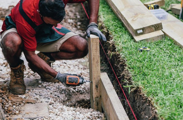 A Bunnings team member bolting a retaining wall to a vertical post