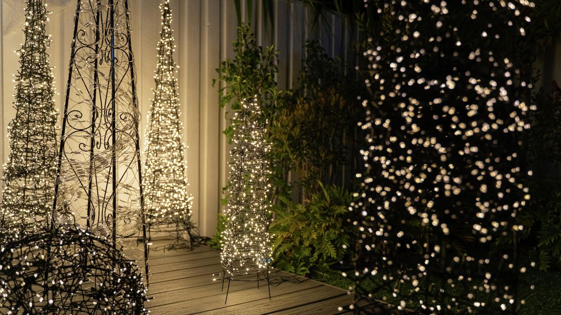 Five Christmas teepees covered in glowing fairy lights sitting on an outdoor deck