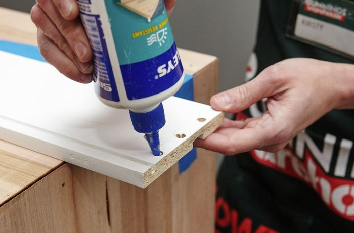 A person applying glue into the holes in a drawer panel