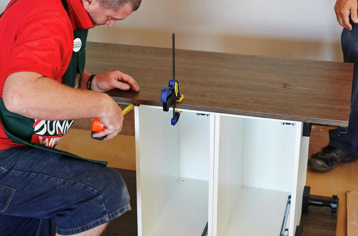 A person attaching a side panel to cabinets using a clamp