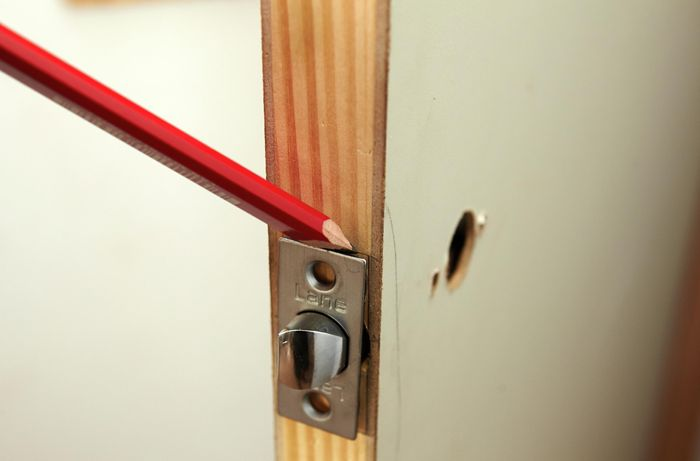 The outline of a door bolt being marked into a door for drilling holes