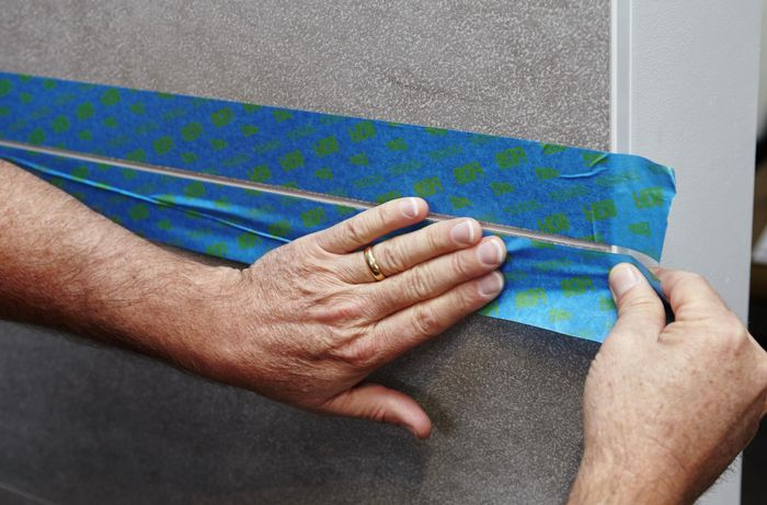 Painters tape being used to protect the tiles from dripping grout sealant