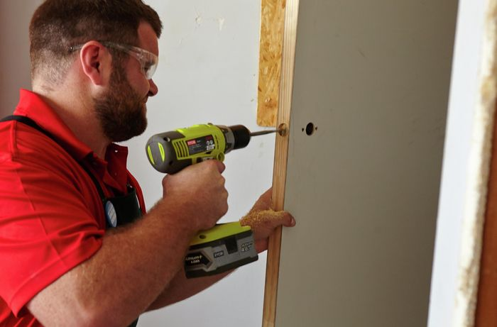 A power drill being used to create a cavity in a door for a door handle