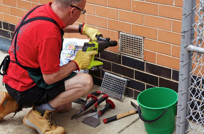 Using your hammer drill to drill through the mortar that holds the old vent in place