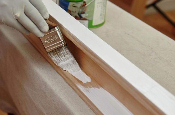 A person painting pine timber white
