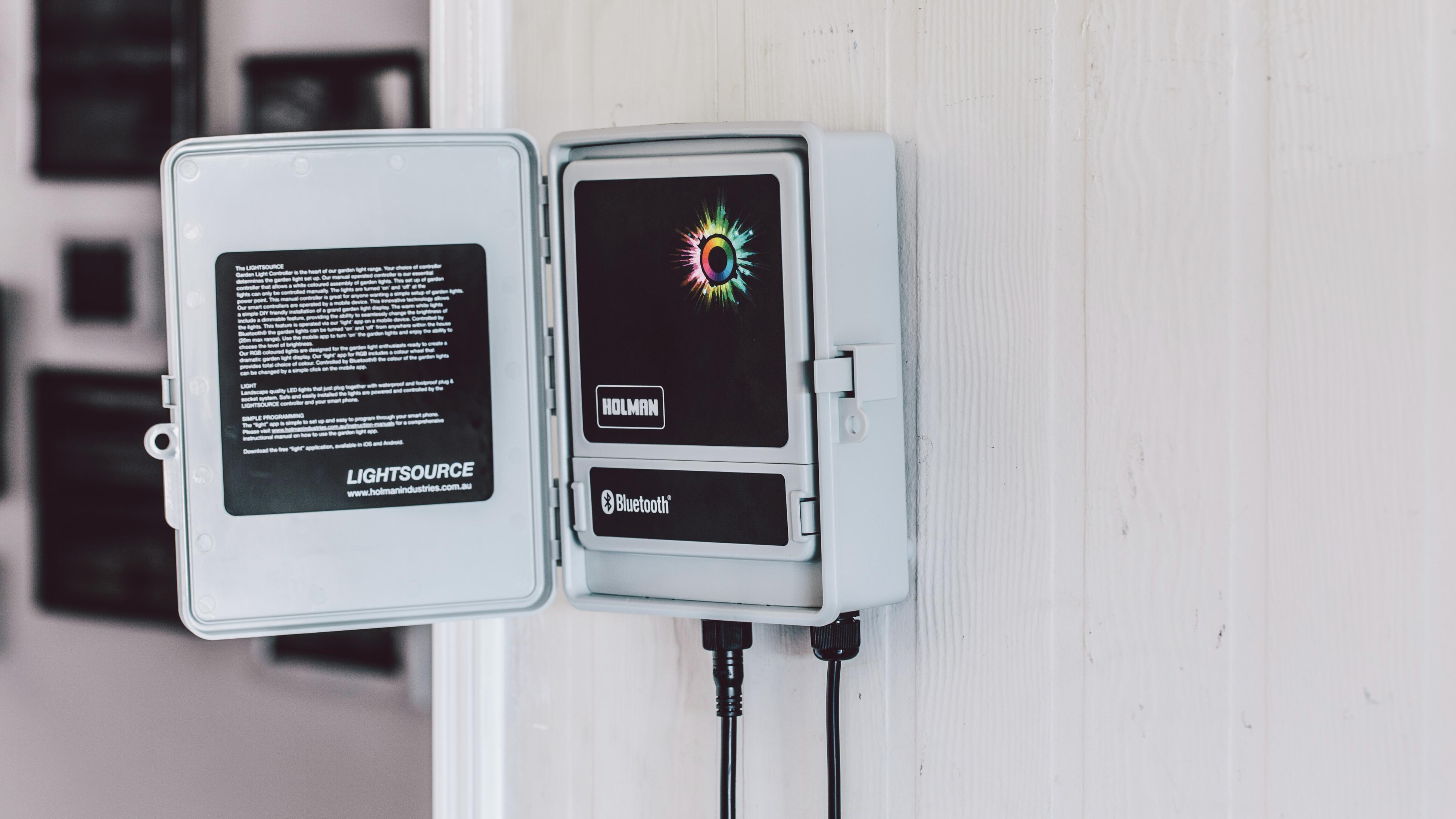 A Holman smart garden control panel attached to a wall.
