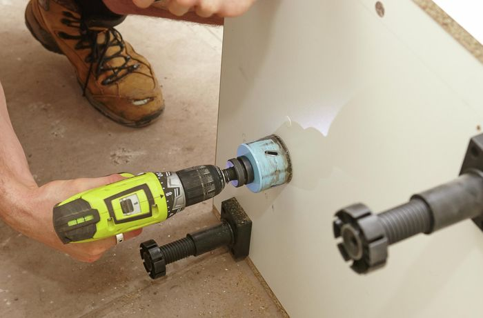 Cutting out a hole for the drain pipe with a drill and hole saw.