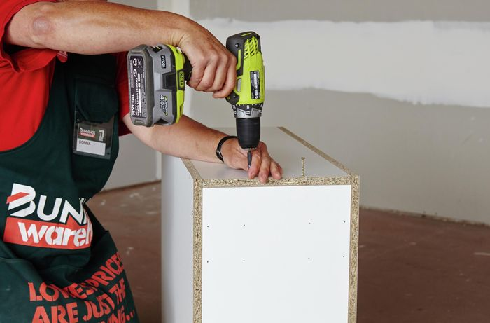 Person attaching panel of cabinet using drill