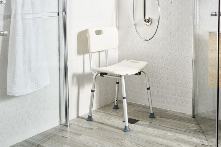 A shower chair in place under a showerhead, with glass doors and hexagonal tiled walls