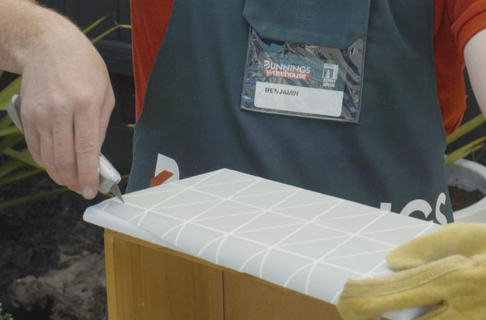 Person cutting wallpaper on the front of a drawer with a utility knife