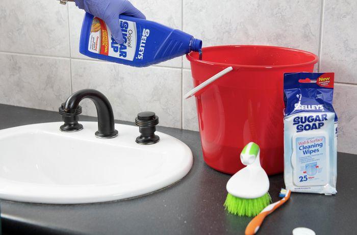 A person pouring sugar soap into a bucket.