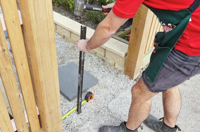 A person using a sledgehammer to insert a star picket in a gravel path