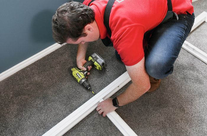 Person using a cordless drill to assemble plantation shutters on the floor