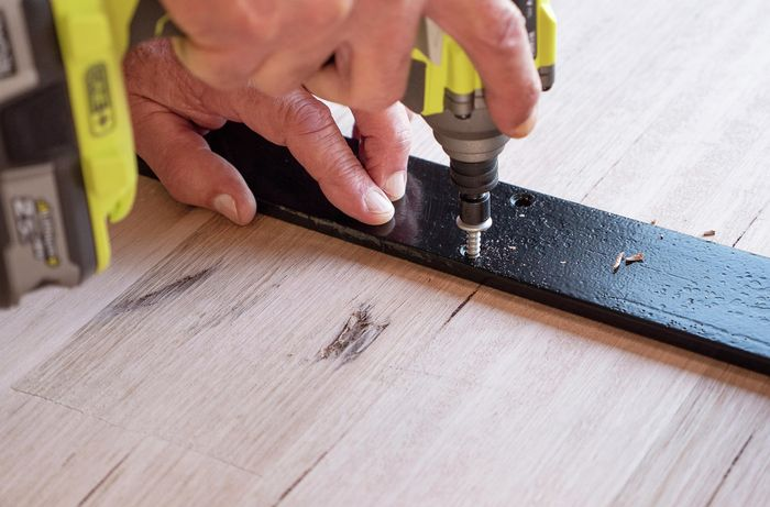 Metal frame being screwed into the underside of a desk top