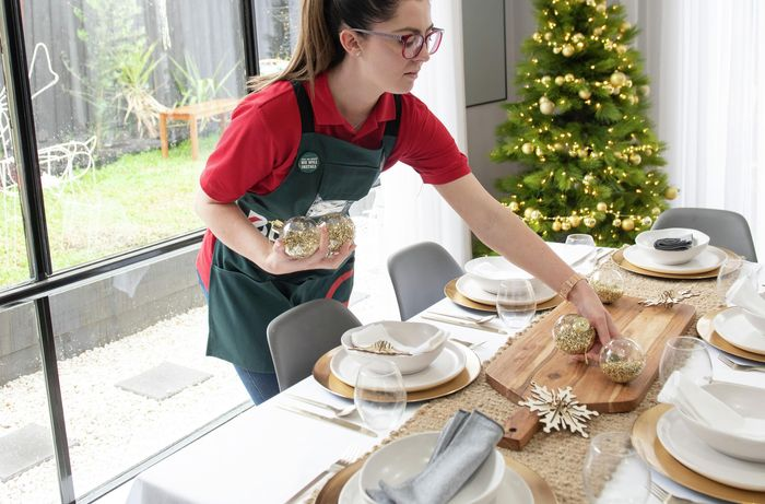 Woman placing bauble decorations around a dining table set for Christmas