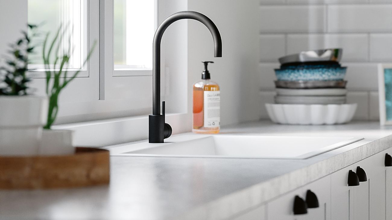 White Hamptons-style kitchen cabinets with matt black handles and curved sink mixer
