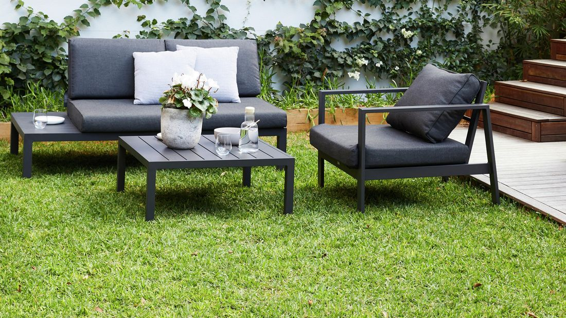 Outdoor furniture on a healthy green lawn next to a garden wall and deck