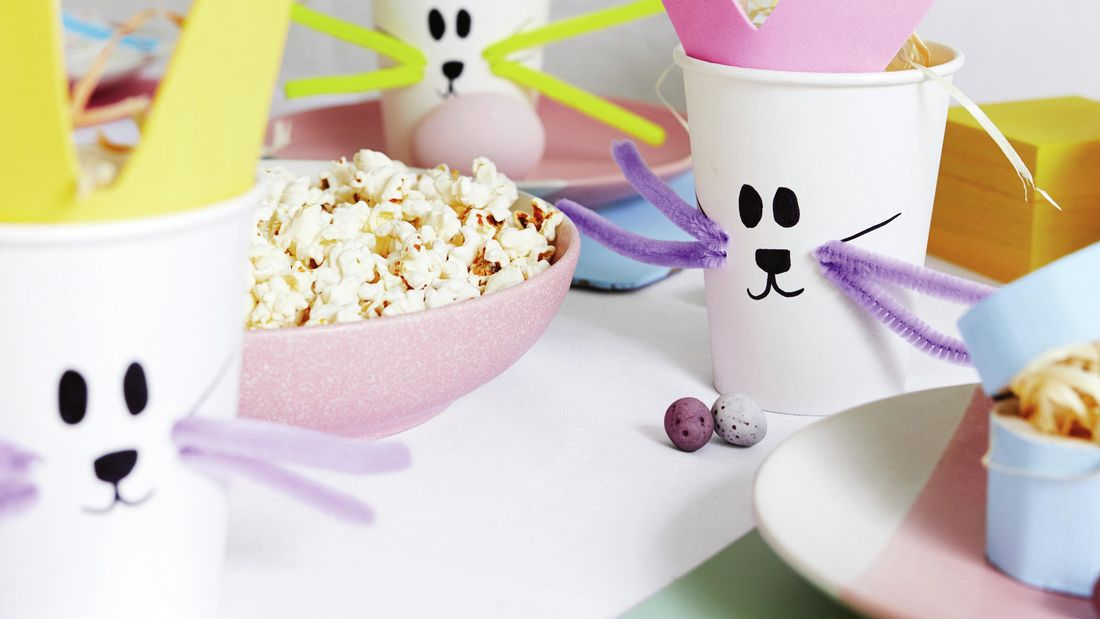 Craft cups with bunny faces on them next to a bowl of popcorn and decorative eggs.