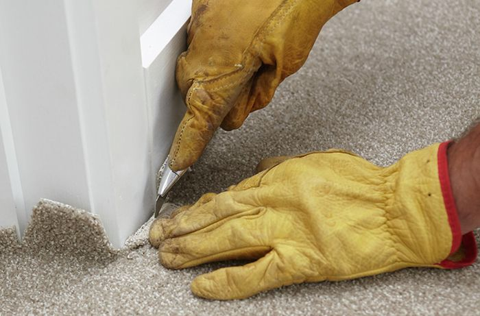 Excess carpet being trimmed from the moulding of a wall