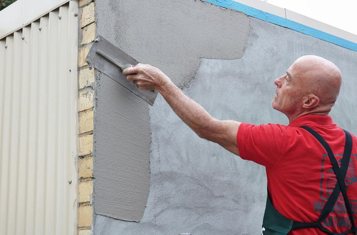 A Bunnings team member applying render to a concrete wall with a trowel