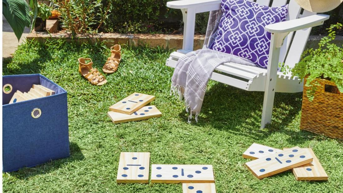 Large dominoes made of plywood on a lawn next to a wooden chair