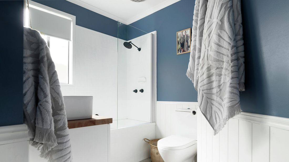 White modern bathroom with plush bath towels, toilet and shower over a bath.