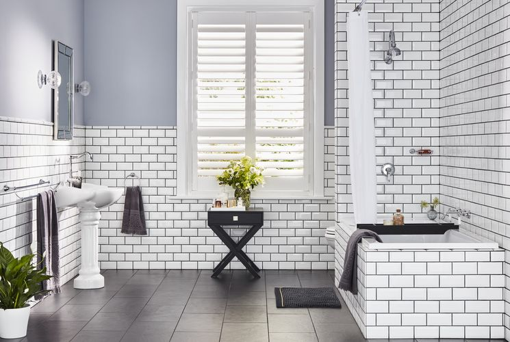 Bathroom with white tiled walls and bath and a sink