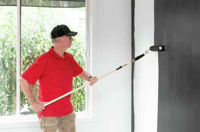 Painting the feature wall with a paint roller