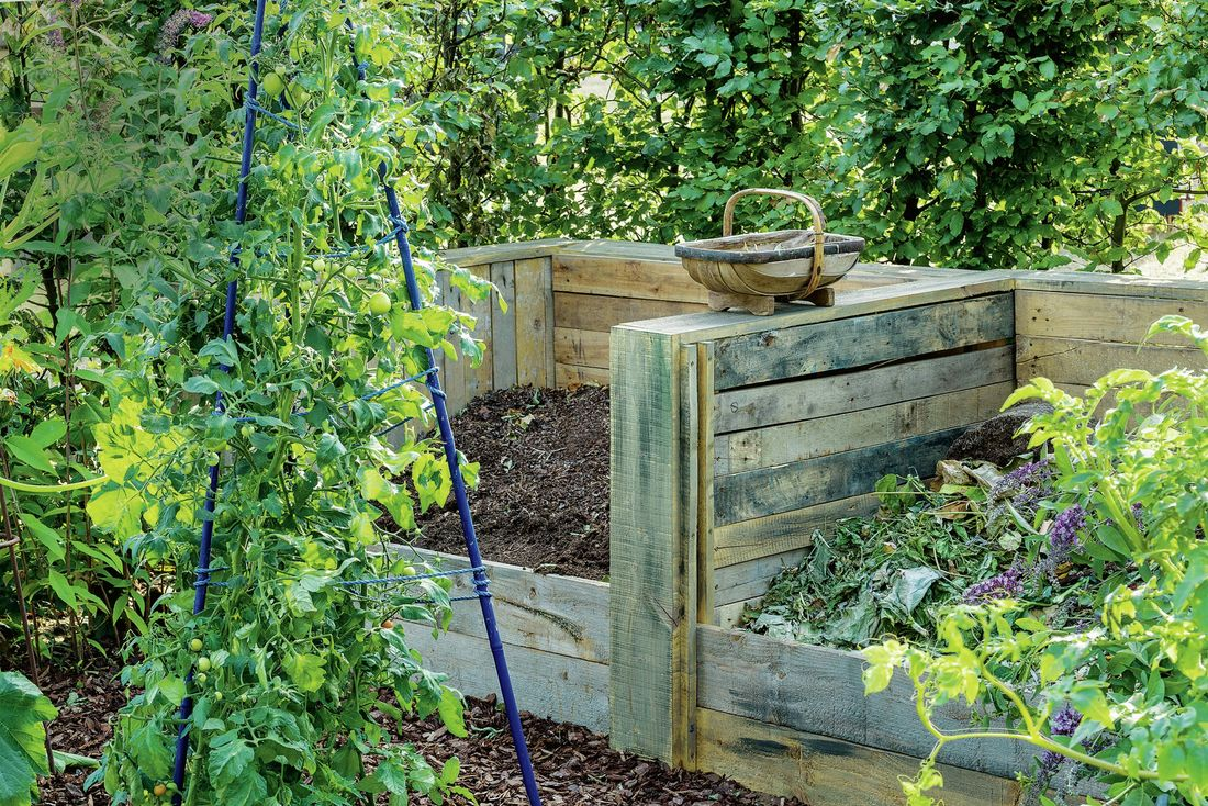 Two large timber compost bins in a back garden
