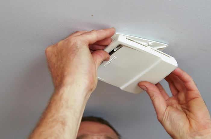 Person removing smoke alarm from roof.