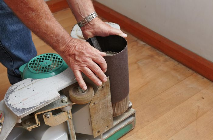 A person fitting a sanding belt to a floor sander