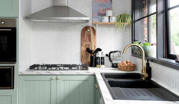 Kitchen with green cupboards and marble benchtop.