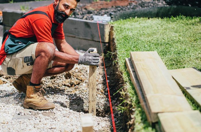 A Bunnings team member securing the vertical post that will hold a retaining wall