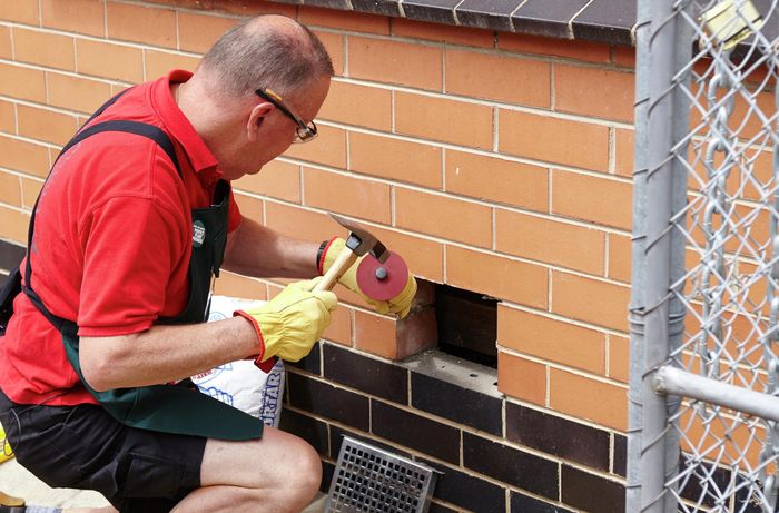 Using a masonry chisel to clear away any excess mortar