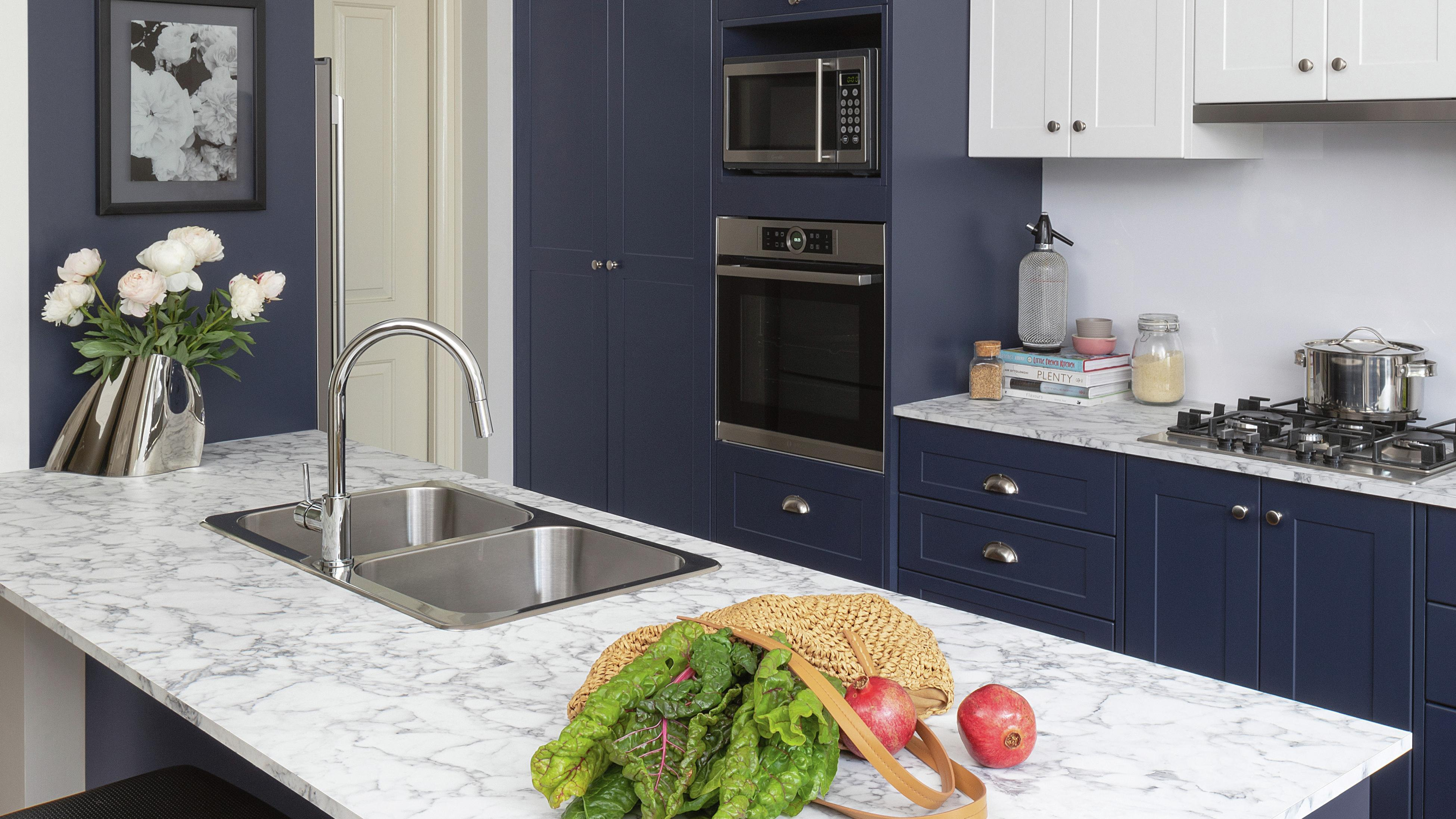 Kaboodle flat pack kitchen featuring marbled-look benchtop and navy cabinetry.