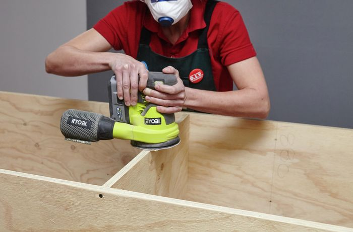 A person sanding the front end of a plywood shelf with an orbital sander
