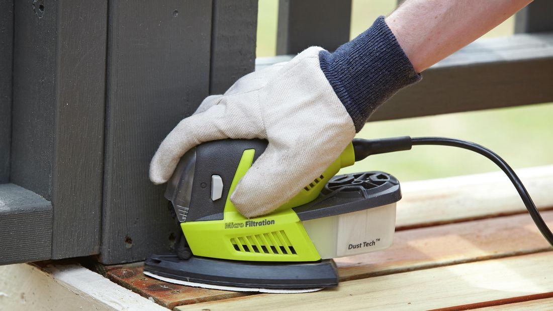 Closeup of a person sanding a deck