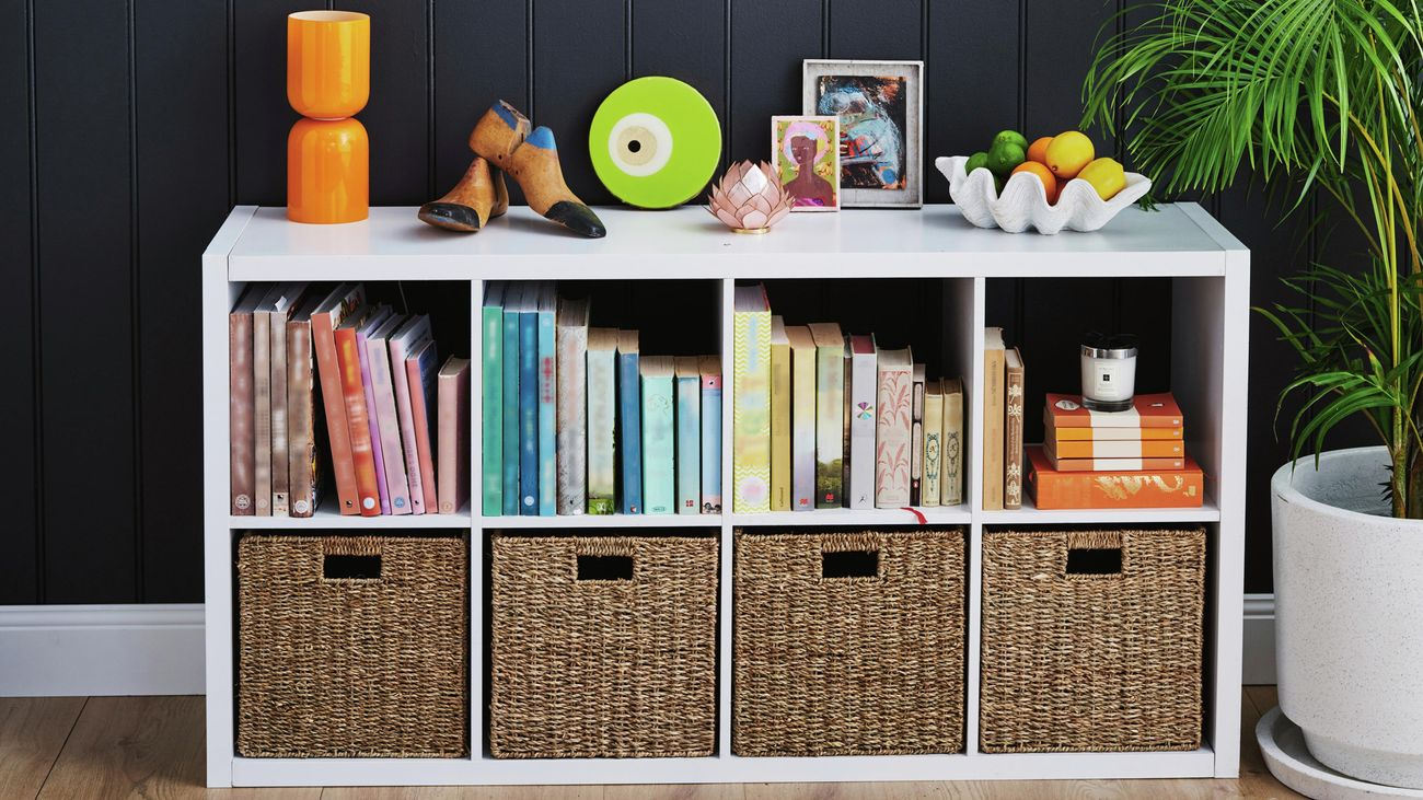 Clever cube shelving with woven inserts, including upright books and ornaments decorated on top of the unit with a bowl of fruit and a round mirror on dark blue backdrop.