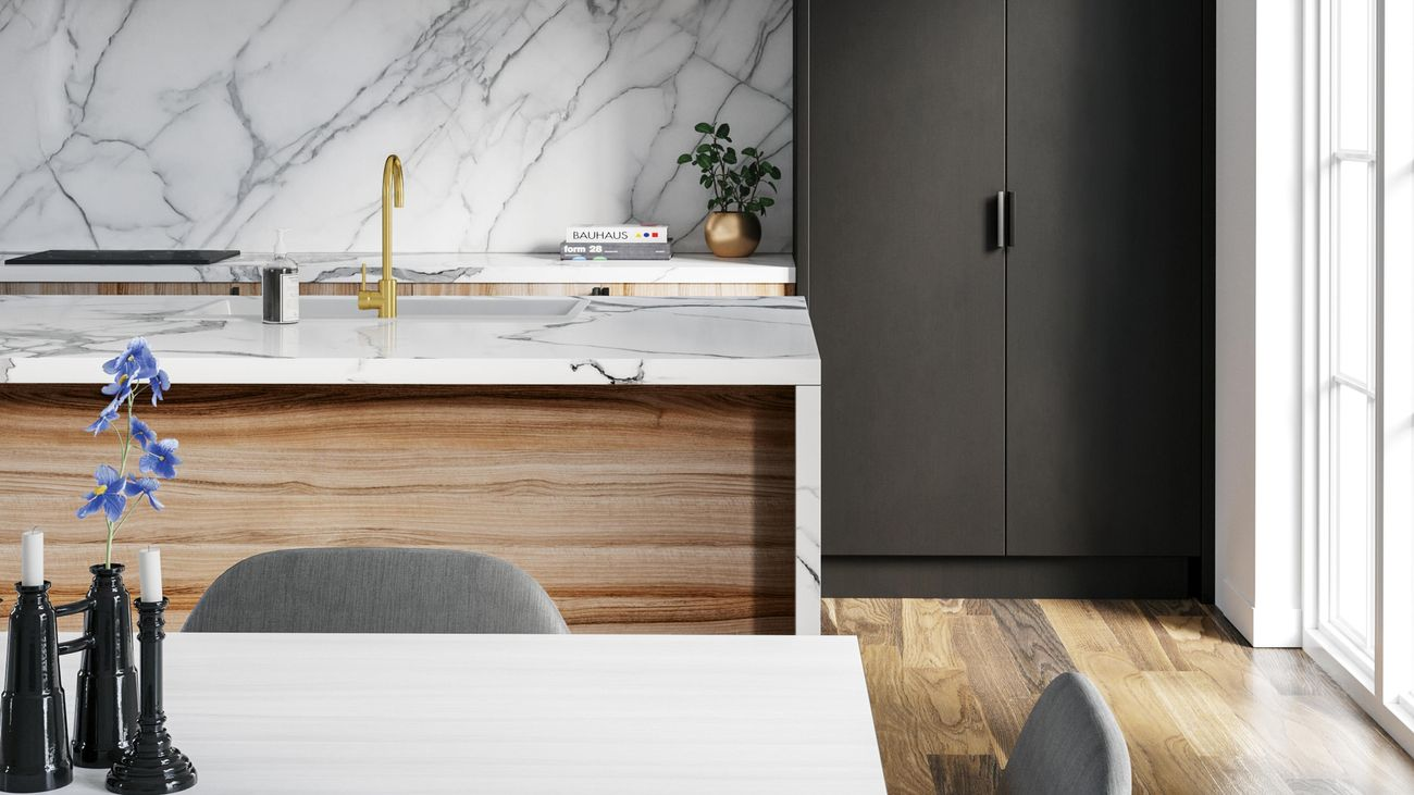 Close up of a full kitchen with model marble bench top, dining table and chairs