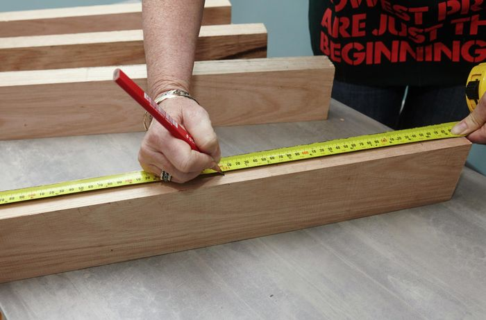 A person measuring and marking length on a piece of timber