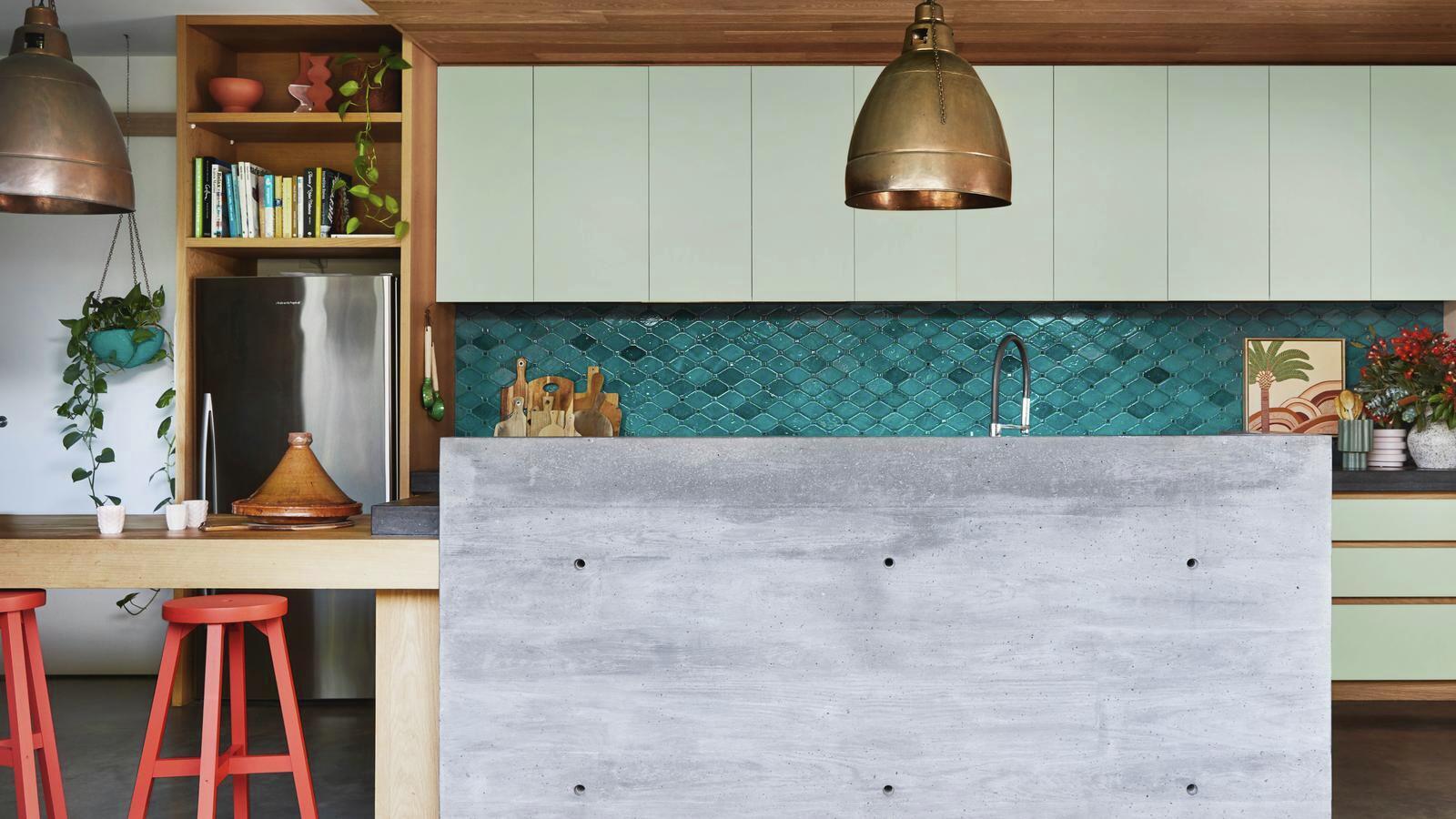 kitchen with blue tiled splashback, gold pendant lights and a concrete benchtop