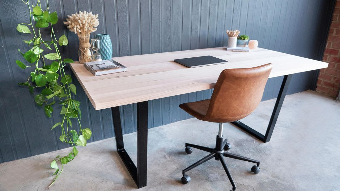 A completed office desk with a leather swivel chair sitting in front of a blue painted wall on concrete floor