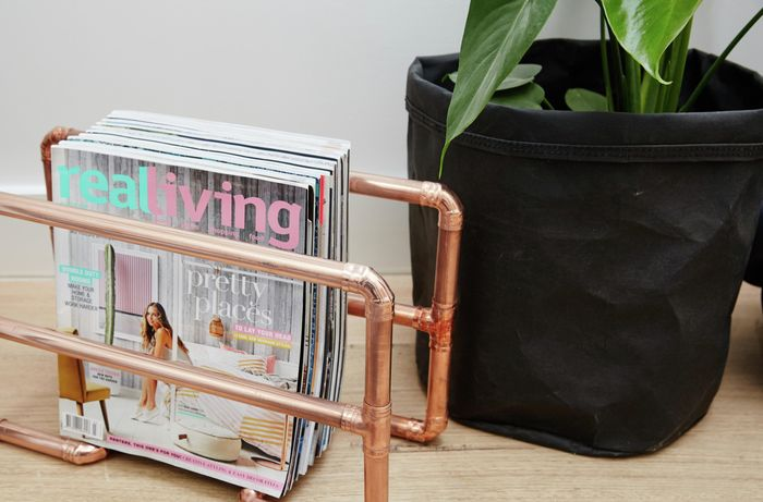 A magazine rack made from polished copper pipe
