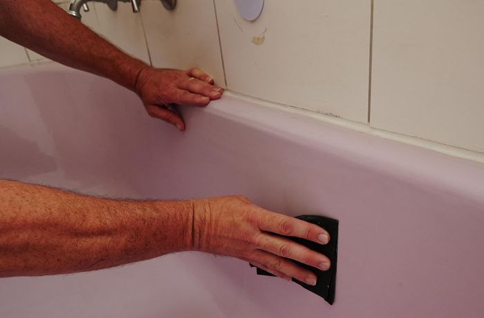 A person sanding a bath with wet and dry sandpaper