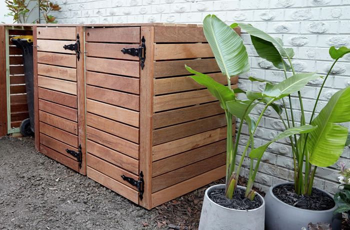 Bin storage unit made of timber, with plants beside.