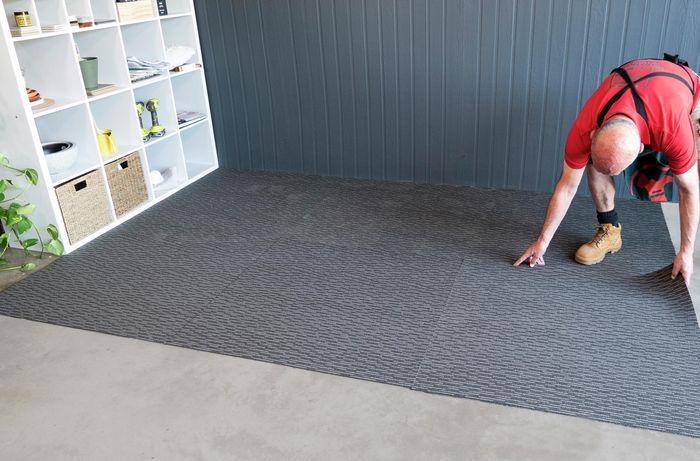 Bunnings team member laying rubber flooring down on a garage floor